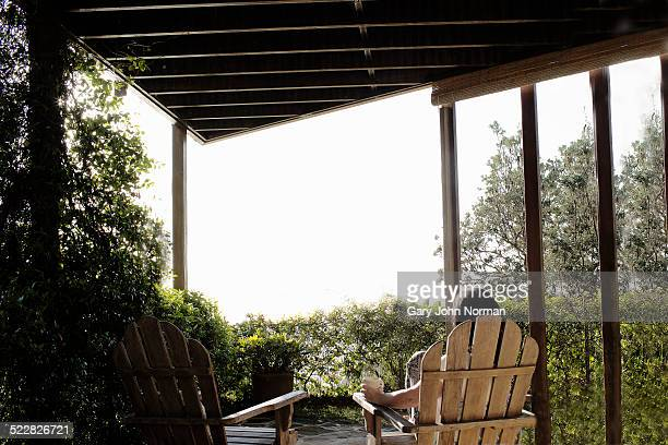 Woman sitting in chair on veranda in morning.