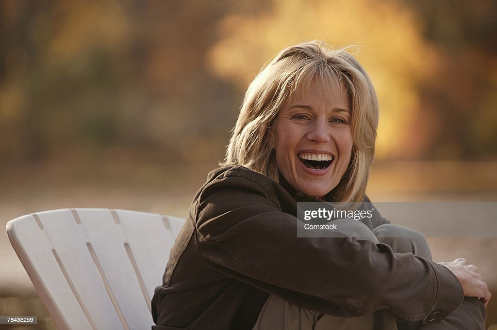 Woman sitting in chair outdoors laughing : Stock Photo