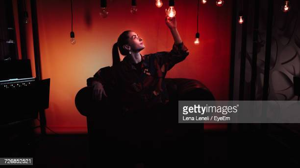 Woman Sitting In Chair Touching Pendant Light