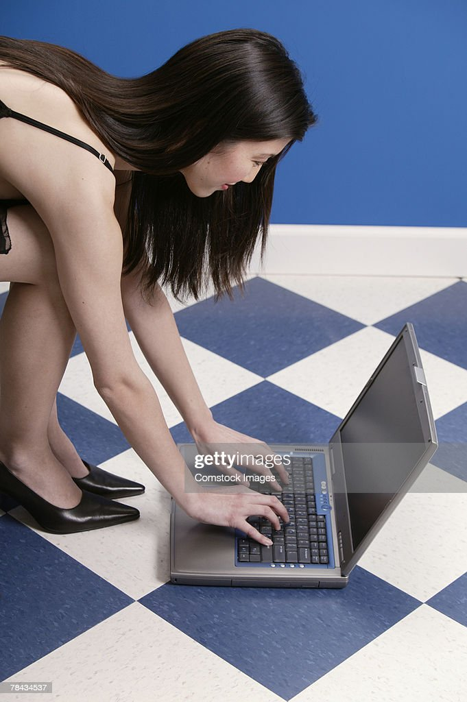Woman sitting in chair , using laptop on the floor : Stockfoto