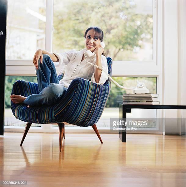 woman sitting in chair, using phone - 加入電話 ストックフォトと画像