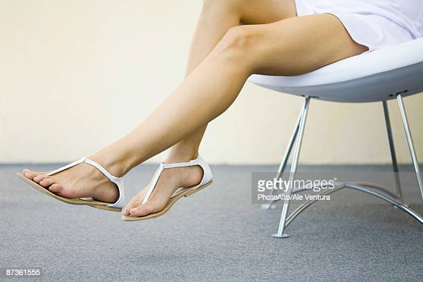 woman sitting in chair with legs dangling, wearing sandals, cropped view - sandalia fotografías e imágenes de stock