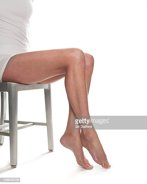 woman sitting in chair with pointed toes - legs crossed at ankle stock pictures, royalty-free photos & images
