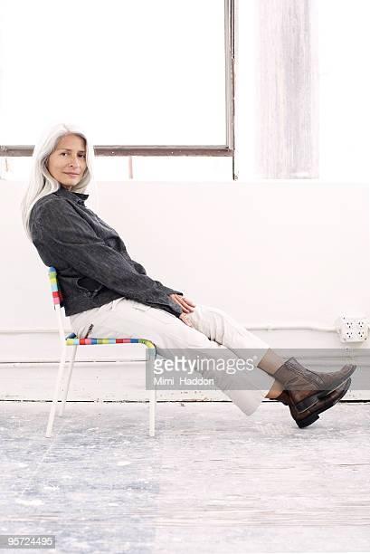 woman sitting in child's chair - サンタモニカ ストックフォトと画像