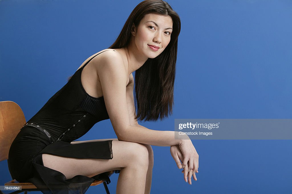 Woman sitting in cocktail dress : Stockfoto
