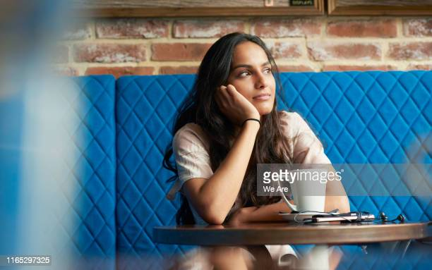 woman sitting in contemplation at a cafe table - contemplation stock pictures, royalty-free photos & images