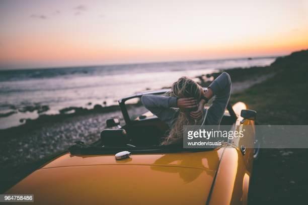 woman sitting in convertible car and looking at the sea - guardare il paesaggio foto e immagini stock