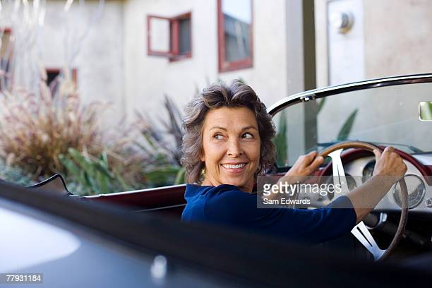 woman sitting in convertible car smiling over her shoulder - leanincollection stock pictures, royalty-free photos & images