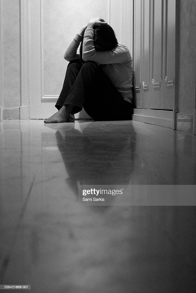 Woman sitting in corridor with head in hands, ground view (B&W) : Stock Photo