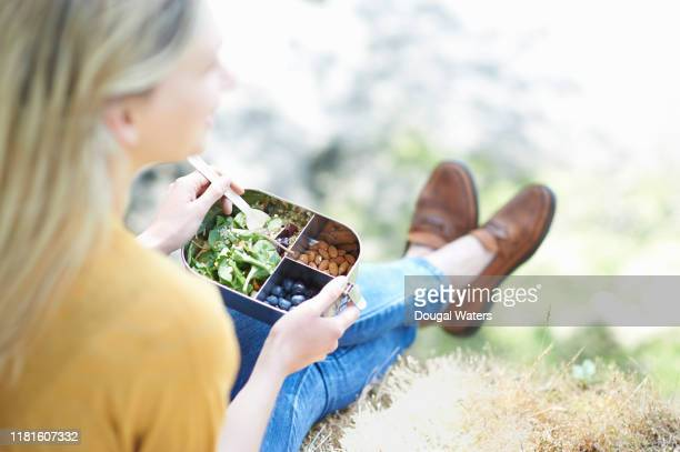 woman sitting in countryside eating healthy plastic free lunch. - healthy eating stock pictures, royalty-free photos & images