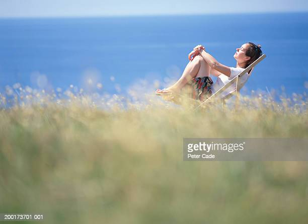 Woman sitting in deck chair by ocean, side view