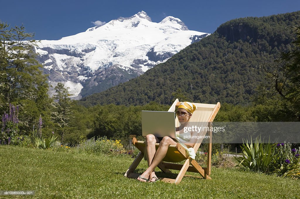 Woman sitting in deck chair, using laptop : Foto stock