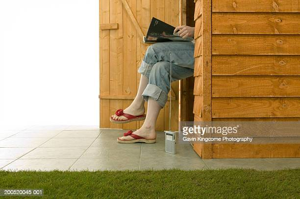 woman sitting in deckchair inside garden shed, reading magazine - rolled up trousers stock pictures, royalty-free photos & images