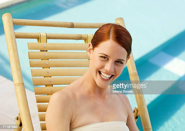woman sitting in deckchair smiling, pool in background - hair part stock pictures, royalty-free photos & images