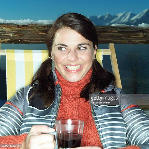 Woman sitting in deckchair with hot drink, close-up