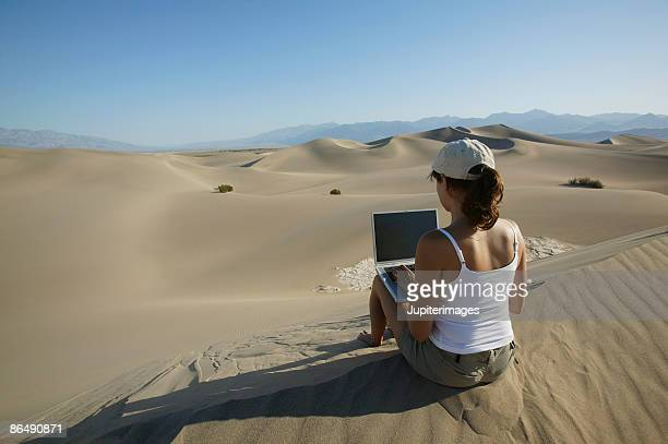 Woman sitting in desert with laptop computer