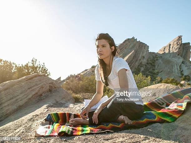 Woman sitting in desert with notebook and pen