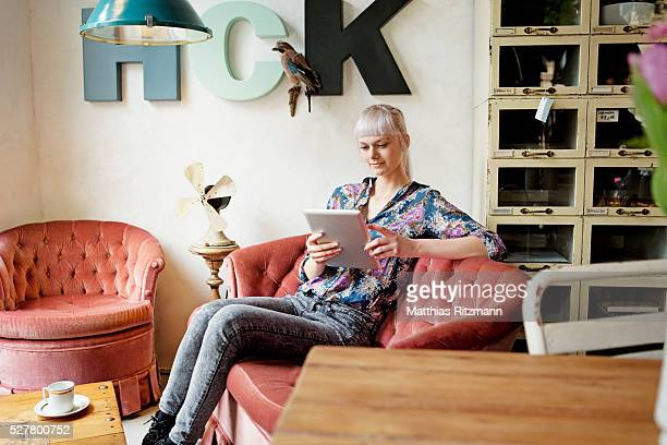 Woman sitting in designer furniture shop and using tablet pc