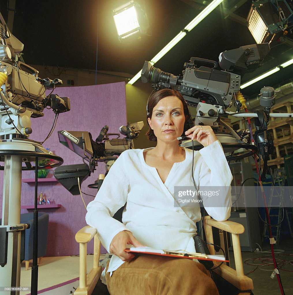 Woman sitting in 'director's chair', cameras in background, portrait : Stock Photo
