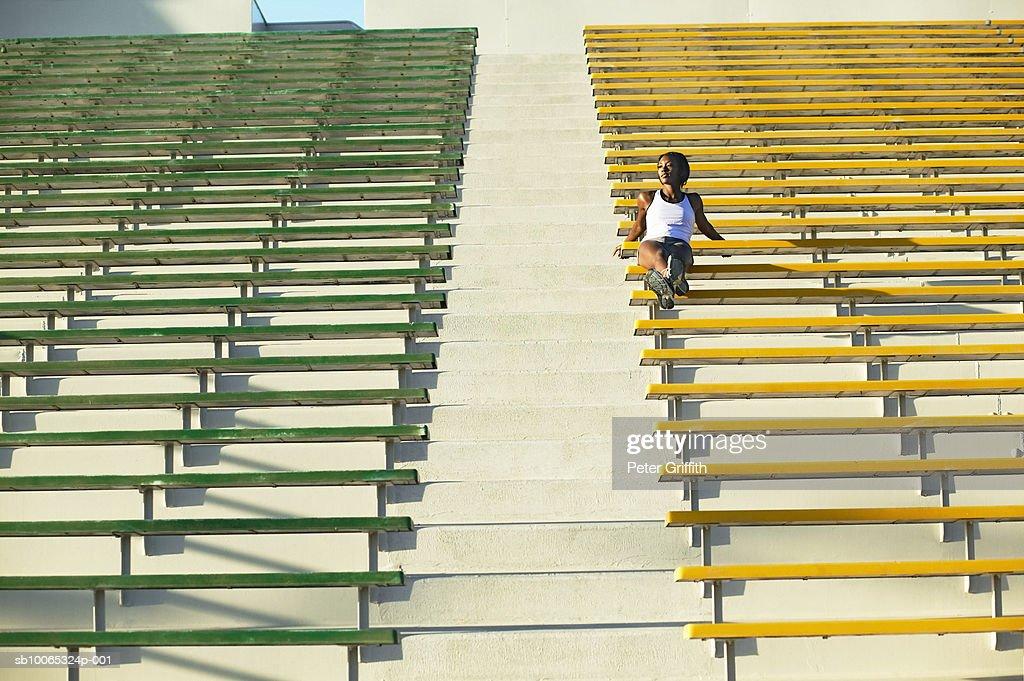 Woman sitting in empty stadium bleachers : Foto stock