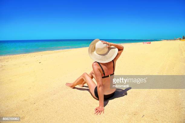 a woman sitting in faro beach on very hot summer day. faro, portugal - faro city portugal stock photos and pictures