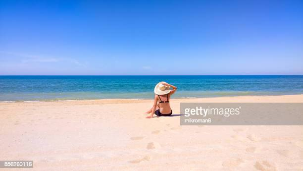 A woman sitting in Faro beach on very hot summer day. Faro, Portugal