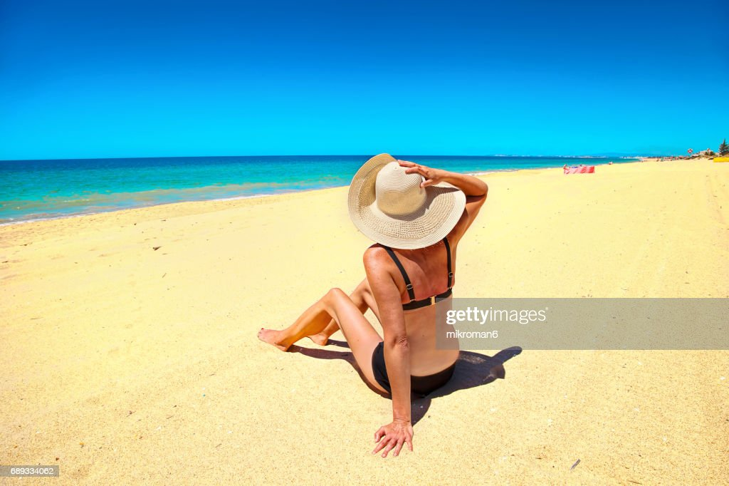 ( EDITORIAL USE ) A woman sitting in Faro beach on very hot summer day. : Stock Photo