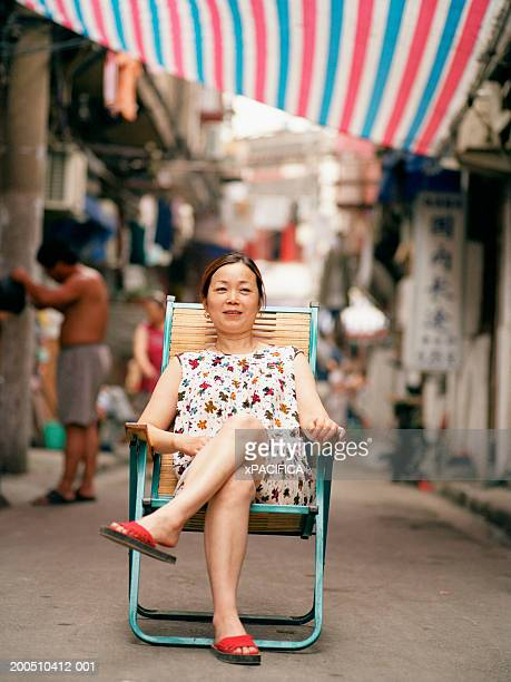 woman sitting in folding chair in alley, portrait - cadeira dobrável - fotografias e filmes do acervo