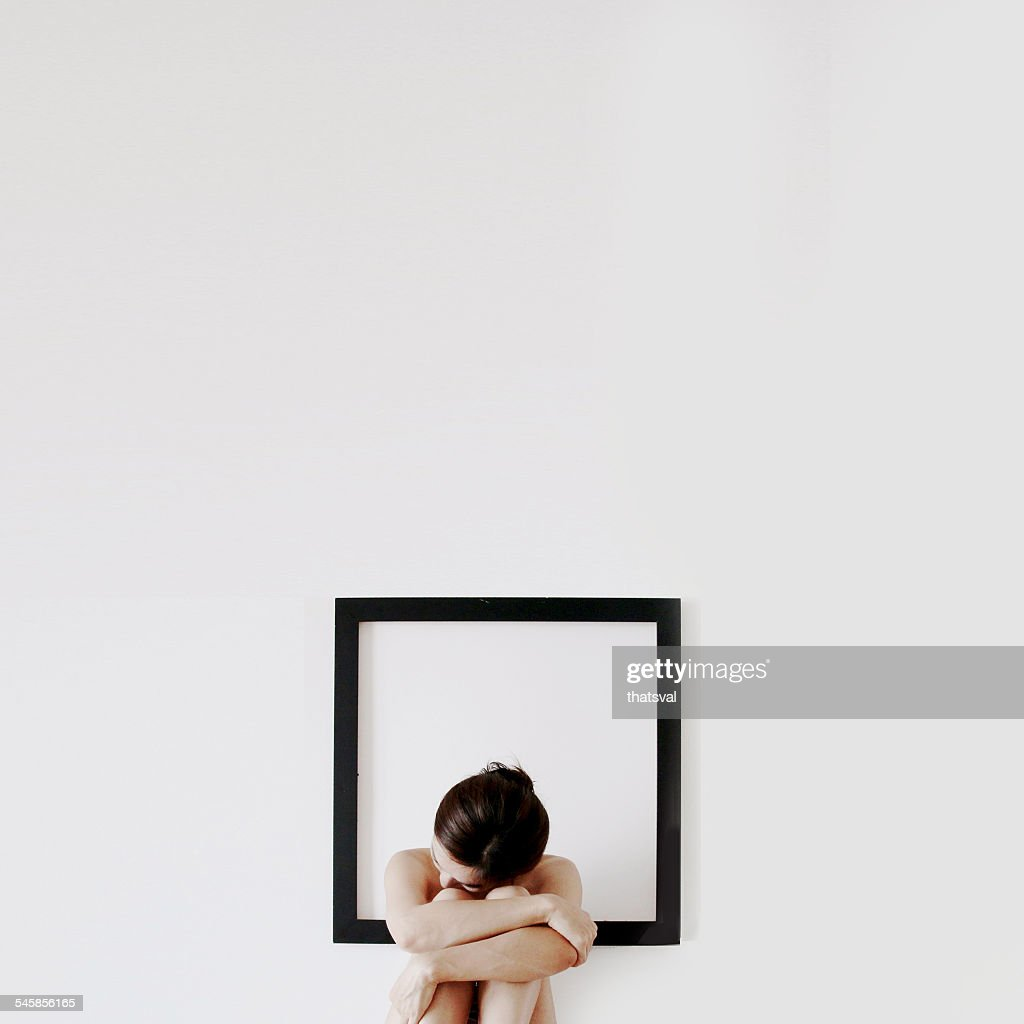 Woman Sitting In Front Of A Blank Picture Frame Hugging Her Knees ...