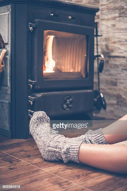 Woman sitting  in front of a wood burning stove