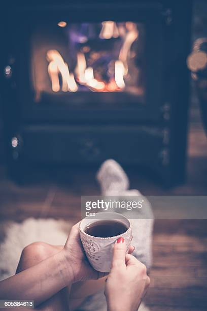 woman sitting in front of a wood burning stove with a cup of coffee - wood burning stove stock photos and pictures