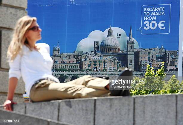 A woman sitting in front of an advertising for a cheap airline flight to the Island of Malta at Plaza Castilla metro station on May 22 2010 in Madrid...