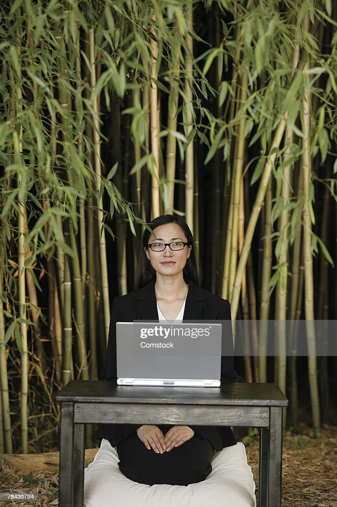 Woman sitting in front of bamboo with laptop computer : Stockfoto
