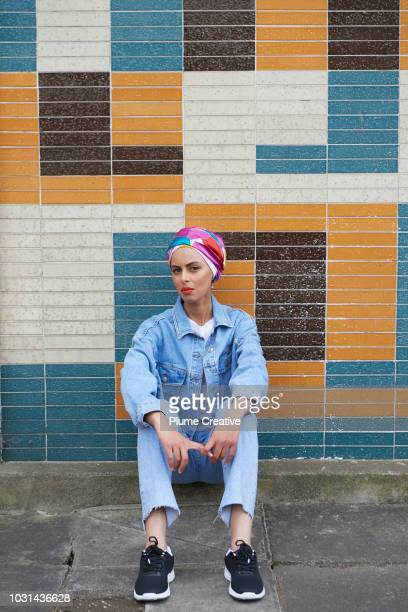 Woman sitting in front of coloured tiled wall