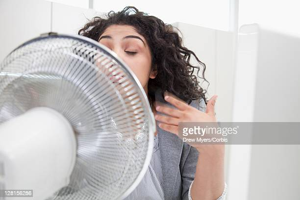 Woman sitting in front of electric fan