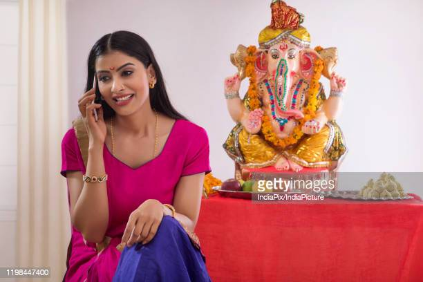 woman sitting in front of ganesh idol talking on mobile phone - hinduism stock pictures, royalty-free photos & images