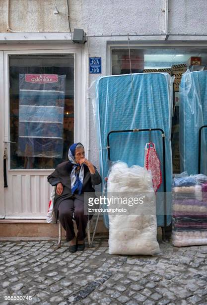 woman sitting in front of her shop in alacati. - emreturanphoto stock pictures, royalty-free photos & images