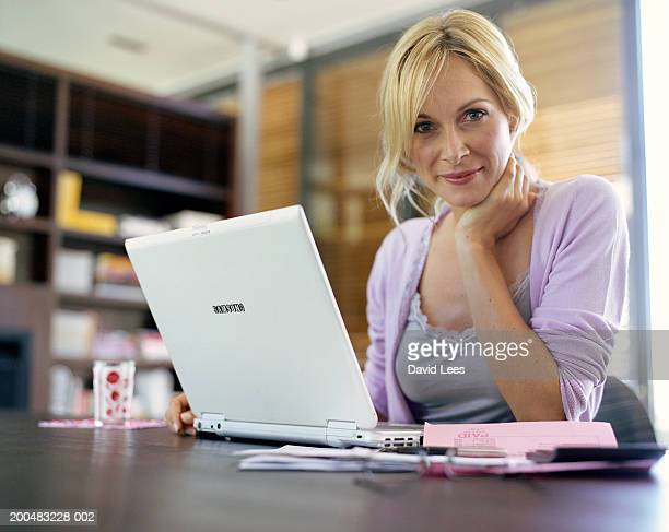 Woman sitting in front of laptop at home, portrait