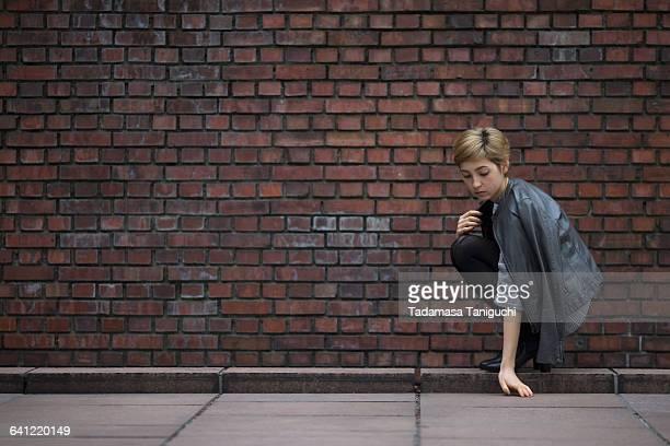 woman sitting in front of red bricks - レザージャケット ストックフォトと画像