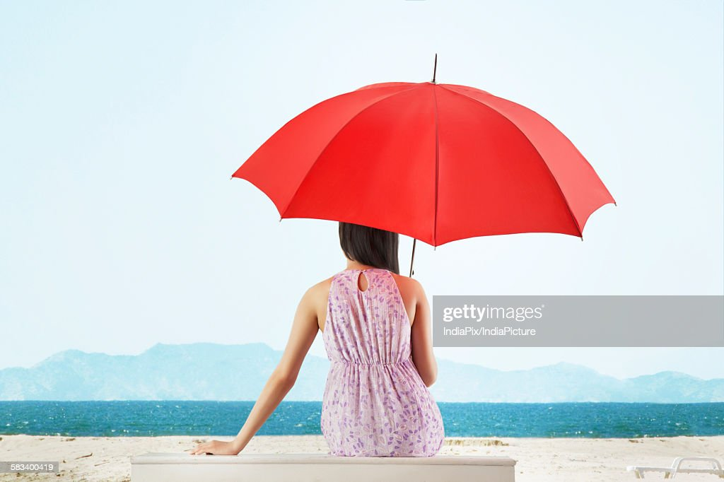 Woman sitting in front of sea with umbrella : Stock Photo