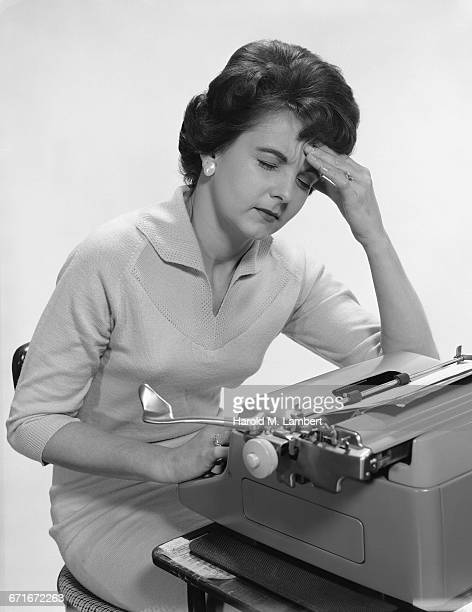 woman sitting in front of typewriter suffering from headache - 30 34 years stock pictures, royalty-free photos & images