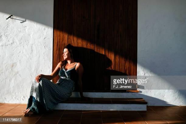 woman sitting in front of typical house door in ibiza. - long dress stock-fotos und bilder