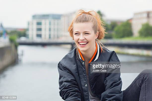 woman sitting in front of water and a bridge - bomber jacket stock pictures, royalty-free photos & images