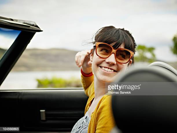 Woman sitting in front seat of convertible