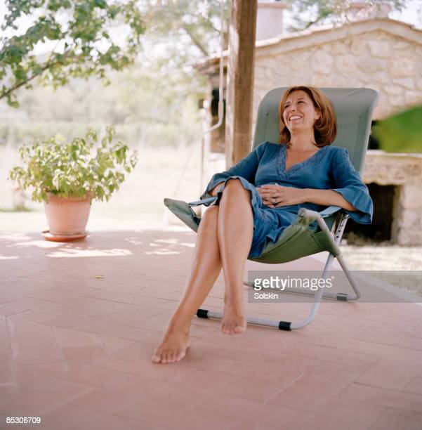 Woman sitting in garden chair, smiling