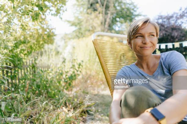 woman sitting in garden on chair - one mid adult woman only stock pictures, royalty-free photos & images