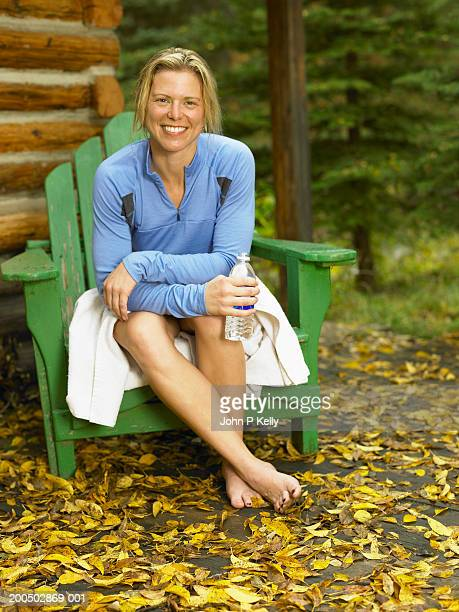 woman sitting in green chair outside log cabin, holding water bottle - コロラド州 ニューキャッスル ストックフォトと画像