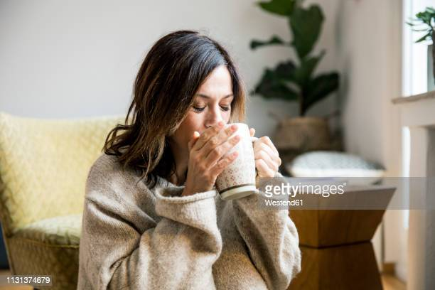 woman sitting in her comfortable home, drinking tea - warme dranken stockfoto's en -beelden