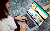 woman sitting in her house with using laptop and booking flight travel search ticket holiday and hotel on website discounted price, concept technology online marketing and promotion.