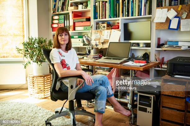 woman sitting in home office - one mid adult woman only stock pictures, royalty-free photos & images